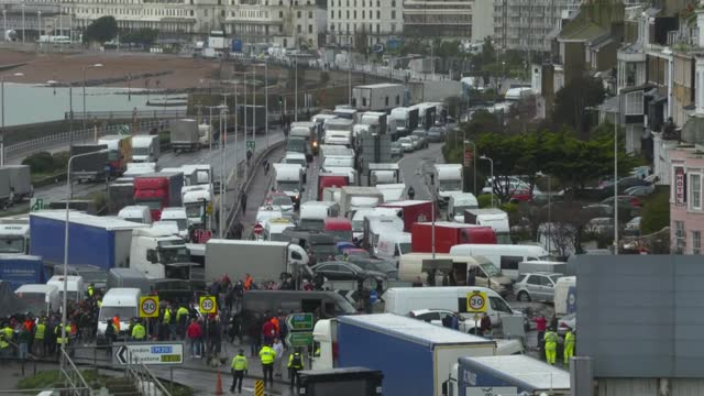 vidéos et rushes de lorries at dover; england: kent: dover: ext / raining people sheltering from the rain in the back of a lorry / traffic at standstill outside port of... - semi remorque