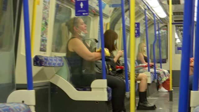 mayor declares masks must still be worn on london transport; manchester and london, uk; various shots of passengers on tube train, with mixture... - protective face mask stock videos & royalty-free footage