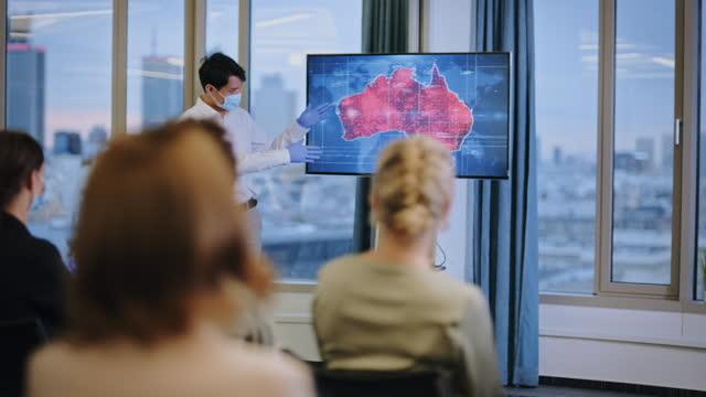 coronavirus-medizin-symposium. junger, asiatischer arzt in gesichtsmaske präsentiert karte von krankheitsausbrüchen in australien - press conference stock-videos und b-roll-filmmaterial