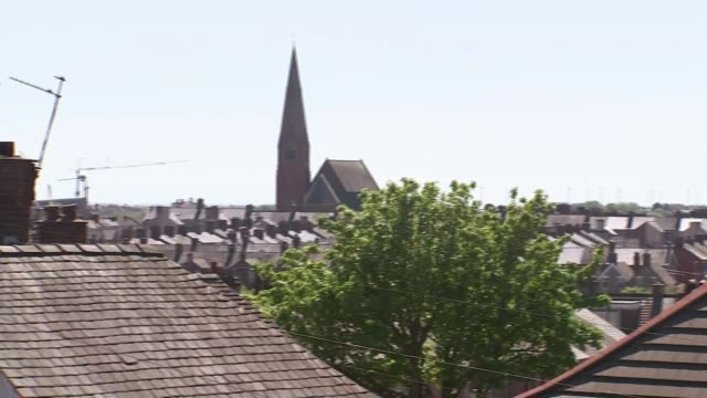 north west of england becomes cornavirus 'hotspot' england cumbria barrowinfurness ext barrow skyline showing rooftops of houses and church spire - church stock videos & royalty-free footage