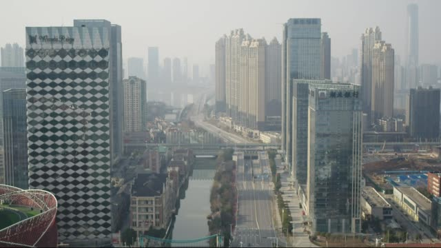 number of new cases falls due to enforced rigorous controls; china: wuhan: ext aerial views cityscape and empty streets during lockdown - quarantena video stock e b–roll