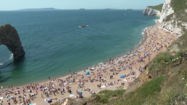 open air markets and car showrooms re-open with social distancing measures; england: dorset: lulworth: durdle door: ext various of crowd on beach - arch stock videos & royalty-free footage