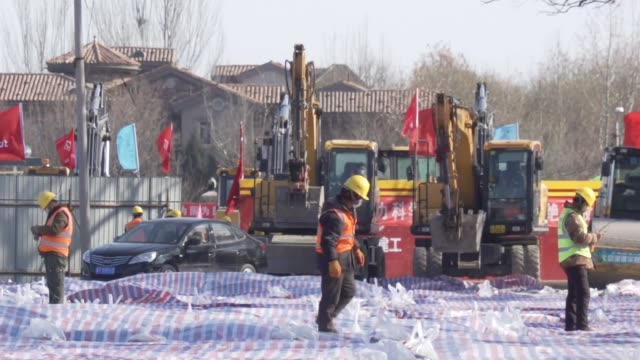 dozens more die from coronavirus in wuhan china beijing / drone footage site of new hospital under construction gv workers on construction site and... - wuhan stock-videos und b-roll-filmmaterial