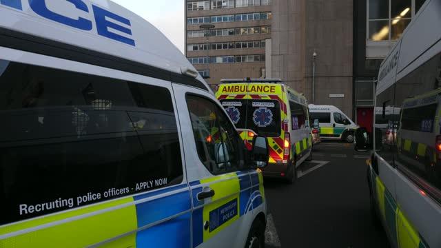 oxford-astrazeneca covid vaccine rollout begins in uk; england: whitechapel: royal london hospital: ext / dusk ambulances parked outside hospital... - hospital stock videos & royalty-free footage