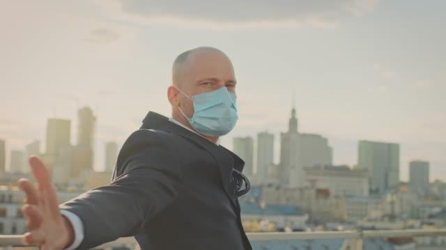 vídeos de stock, filmes e b-roll de pandemia coronavírus. empresário conquistando mundo pandêmico - mãos estendidas