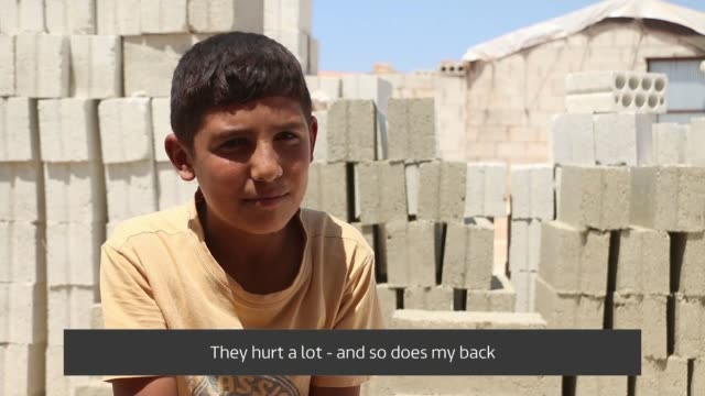 pandemic forces refugee children into work; syria: int mohammed operating sewing machine feet on pedal boys making face masks with sewing machines... - needle plant part stock videos & royalty-free footage