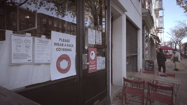 """vidéos et rushes de coronavirus pandemic signage in brooklyn on the window by the entrance to a restaurant in cobble hill / brooklyn heights. """"please wear a face... - panneau d'entrée"""