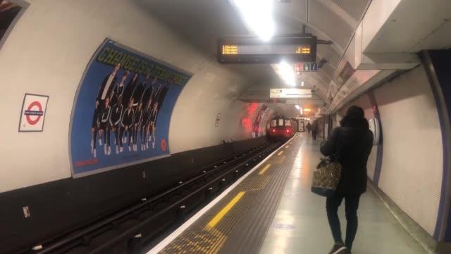 people begin to return to work: london underground; england: london: king's cross st pancras: track down escalator / train leaving station / train... - railway track stock videos & royalty-free footage