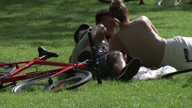 people in hackney park gvs; england: london: hackney: ext various of groups of people sitting on grass in the sunshine in busy park / - sunlight stock videos & royalty-free footage