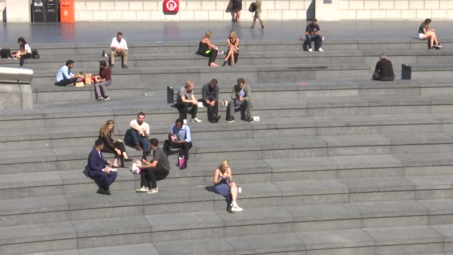 people relaxing in the sun near tower bridge gvs; england: london: tower bridge / city hall: ext gv people sitting on grass outside city hall and... - lunch stock videos & royalty-free footage