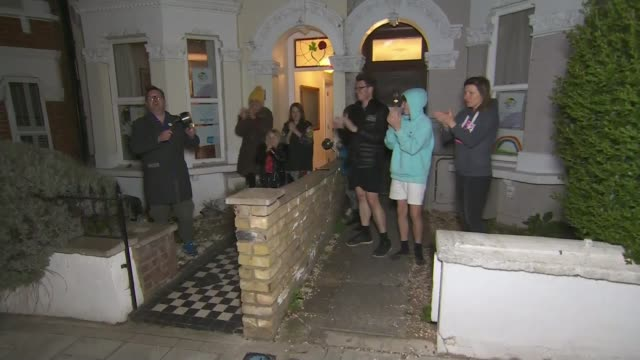 people stand on doorsteps to applaud nhs workers and others helping tackle the disease england london earlsfield people gathered outside their houses... - nhs stock videos & royalty-free footage