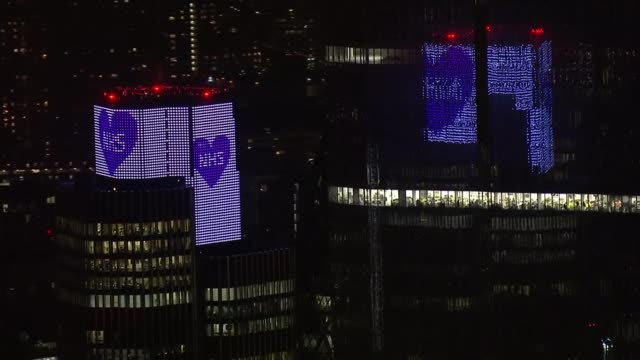 people stand on doorsteps to applaud nhs workers and others helping tackle the disease; uk, london: london landmarks lit up in blue to pay tribute to... - nhs stock videos & royalty-free footage