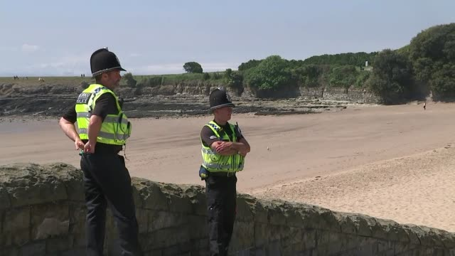 stockvideo's en b-roll-footage met people throng to beaches and beauty spots in hot weather amid concerns about social distancing; wales: barry: ext police officers stood overlooking... - bord weg afgesloten