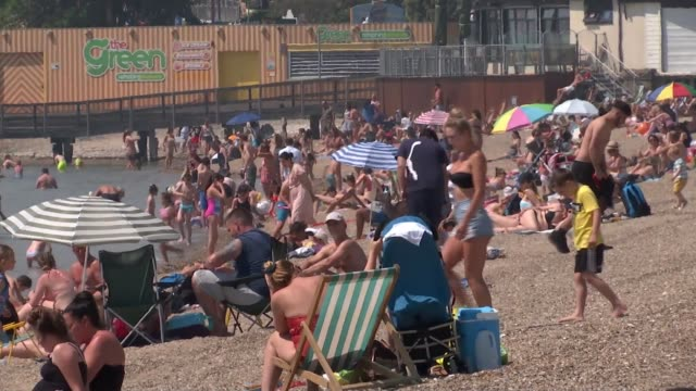 people throng to beaches and beauty spots in hot weather amid concerns about social distancing; england: essex: southend: ext crowded beach in the... - england stock videos & royalty-free footage