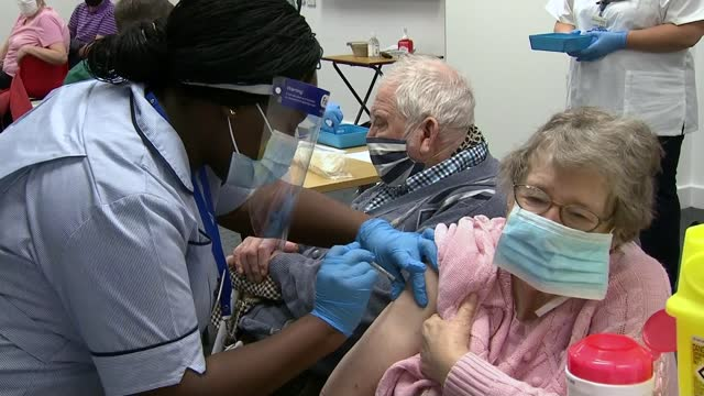 pfizer vaccine roll-out begins across uk; england: buckinghamshire: milton keynes university hospital: reporter to camera close shot 'milton keynes... - technician stock videos & royalty-free footage