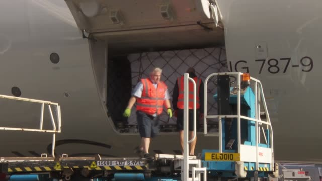 plane carrying ppe shipment from china arriving; england: london: hillingdon: heathrow airport: ext gvs of staff unloading of ppe packages / int... - shipping stock videos & royalty-free footage