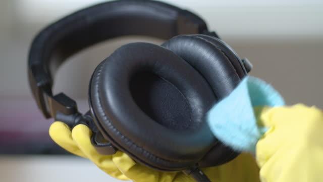vídeos de stock, filmes e b-roll de proteção contra coronavírus. limpando os fones de ouvido. mantenha tudo limpo e desinfetado. importância da higiene. - anti higiênico