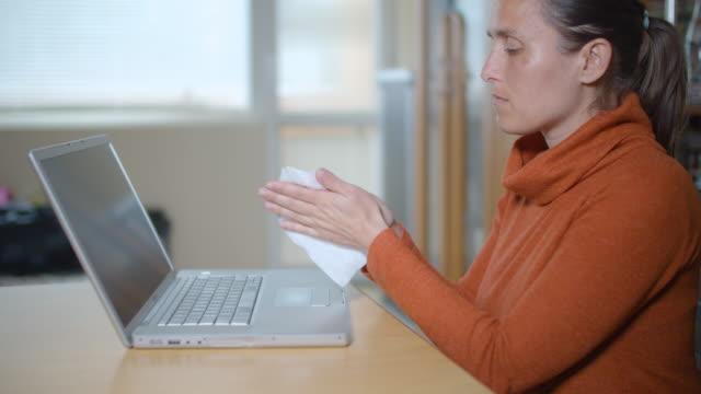 vídeos de stock, filmes e b-roll de proteção contra coronavírus. limpando o laptop antes de começar a trabalhar. trabalhando em casa. mantenha tudo limpo e desinfetado. importância da higiene. - anti higiênico