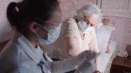 Coronavirus protection during the quarantine. Female doctor giving vaccination to a senior woman at her home.