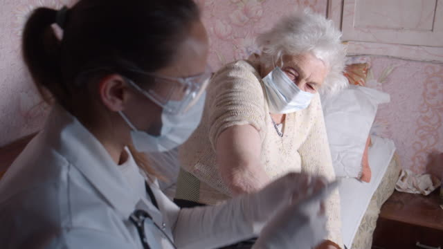 coronavirus protection during the quarantine. female doctor giving vaccination to a senior woman at her home. - protective workwear stock videos & royalty-free footage