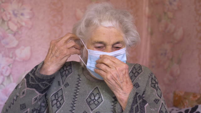 coronavirus protection. senior woman wearing mask to avoid infectious diseases. - epidemia video stock e b–roll