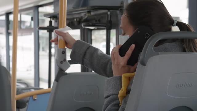 vídeos de stock, filmes e b-roll de proteção contra coronavírus. mulher com uma máscara protetora falando ao telefone enquanto viajava no ônibus. - anti higiênico