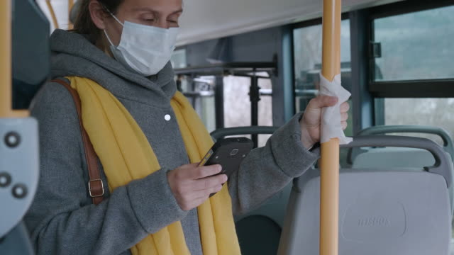 coronavirus protection. woman with a protective mask to avoid infectious diseases, surfing the internet while  in the bus shuttle. - bus stop stock videos & royalty-free footage
