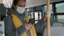 Coronavirus protection. Woman with a protective mask to avoid infectious diseases, surfing the internet while  in the bus shuttle.