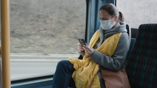 coronavirus protection. woman with a protective mask to avoid infectious diseases, surfing the internet while  in the bus shuttle. - day in the life stock videos & royalty-free footage