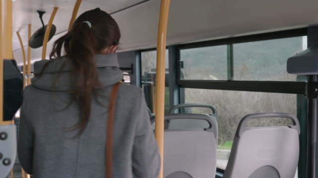 vídeos de stock e filmes b-roll de coronavirus protection. woman with a protective mask to avoid infectious diseases, surfing the internet while  in the bus shuttle. - autocarro