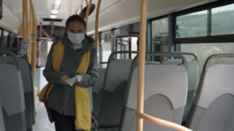 coronavirus protection. worried woman with a protective mask on her face traveling with bus after work. - day in the life series stock videos & royalty-free footage