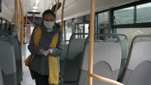 vídeos de stock e filmes b-roll de coronavirus protection. worried woman with a protective mask on her face traveling with bus after work. - um dia na vida de