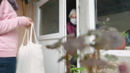 Coronavirus protection. Young adult doing food deliveries, groceries and supplies to a senior woman. Illness prevention. People with protective mask on their faces.