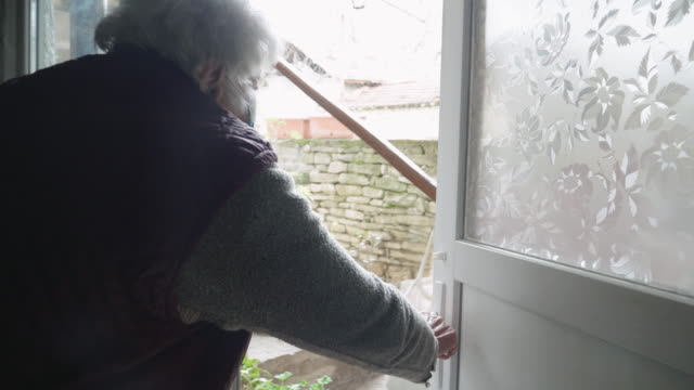 coronavirus protection. young adult doing food deliveries, groceries and supplies to a senior woman. illness prevention. people with protective mask on their faces. - prevenzione delle malattie video stock e b–roll