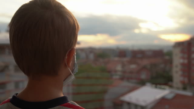 covid-19 - coronavirus quarantine - young boy looking trough the window - uncertainty stock videos & royalty-free footage