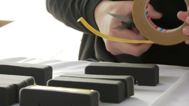 royal mint makes visors for the nhs; wales: llantrisant: int various of workers at the royal mint making protective visors nhs workers staff tackling... - 王立鋳貨局点の映像素材/bロール