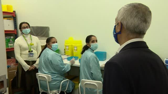 sadiq khan visits vaccination hub in croydon; england: london: croydon: int sadiq khan along with hospital staff in vaccination centre / khan meeting... - technician stock videos & royalty-free footage