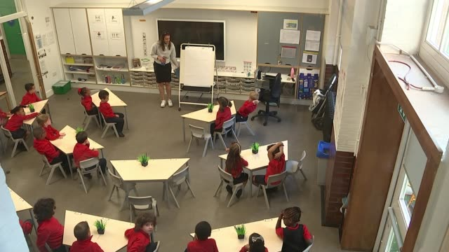 schools reopen in england; england: london: borough: charles dickens primary school: int high angle shot of year one pupils in classroom with teacher... - classroom stock videos & royalty-free footage