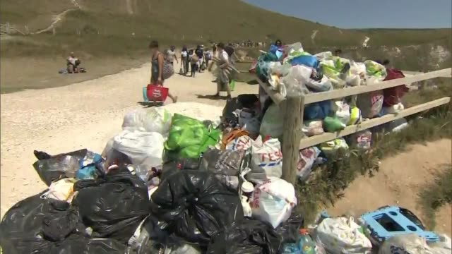 'second spike' concerns as crowds flock to beaches on hottest day of the year; england: dorset: ext crowds on busy durdle door beach during heatwave.... - arch stock videos & royalty-free footage