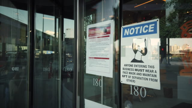 coronavirus sign on door of a business in new york city notice everyone entering this business must wear a face mask and maintain 6 feet of... - home showcase interior stock videos & royalty-free footage