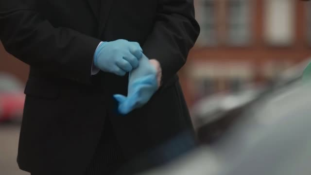 social distancing measures affecting funerals; england: leicestershire: ext undertakers putting on protective rubber gloves and getting into car - funeral stock videos & royalty-free footage
