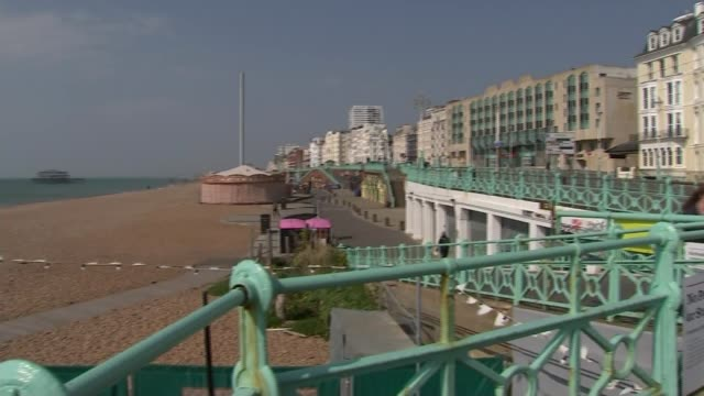 social distancing measures update from brighton; england: east sussex: brighton: ext tracking shot across promenade showing deserted beach metal... - servizio segmento produzioni video stock e b–roll