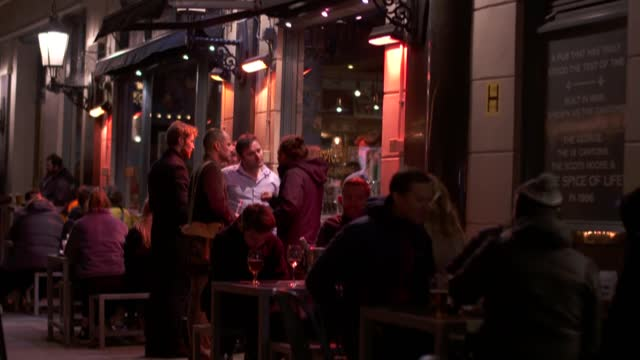 soho nighlife on eve of lockdown; england: london: soho: ext / night people eating in restaurant / people eating on bench / people eating in seating... - couple relationship stock videos & royalty-free footage