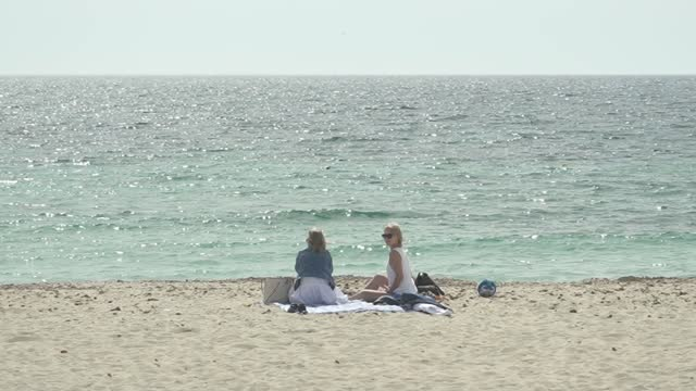 spain to lift travel restrictions for british tourists but remains on uk government's amber list; spain: ext two women sitting on beach - spain stock videos & royalty-free footage