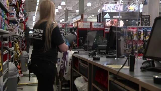 stockvideo's en b-roll-footage met sport direct store on first day of reopening england ext gvs sport direct store / social distancing rules/advice signs worker at 'cleaning station'... - afwashandschoen