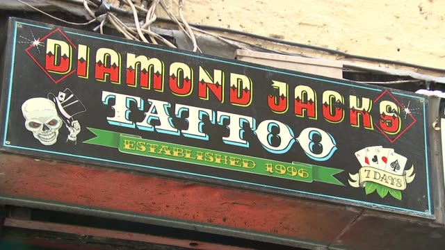 tattoo studios allowed to re-open; england: soho: walker's court: ext neon sign 'tattoo' in window man along past vape store, tattooist and adult... - living room stock videos & royalty-free footage