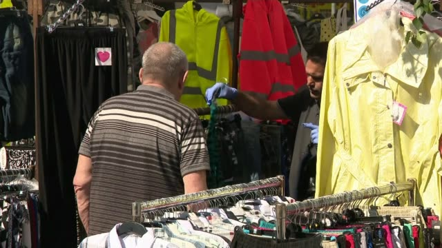 test and trace data leaked to channel 4 news england yorkshire barnsley ext '2m' sign on market stall men looking at clothes on stall various shots... - politics stock videos & royalty-free footage