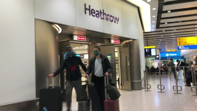 vídeos de stock, filmes e b-roll de three cities now on unprecedented lockdown as country scrambles to contain virus england london heathrow airport int two passengers through airport... - máscara cirúrgica