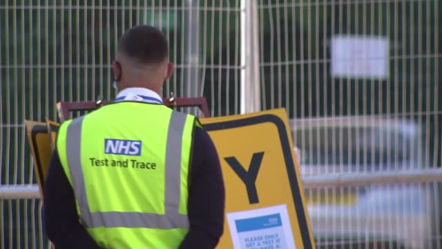 government labs struggling to cope with backlog of almost 200,000 tests; england: london: ext poster attached to fence steward wearing 'nhs test and... - poster stock videos & royalty-free footage