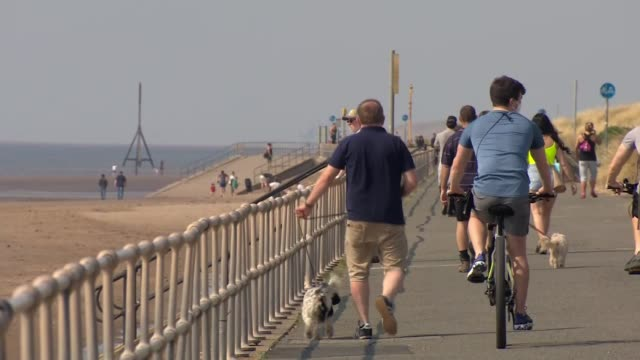 uk hospital death toll passes 20000 england merseyside ext people walking dogs and cycling along sea front people sitting on beach - beach stock videos & royalty-free footage